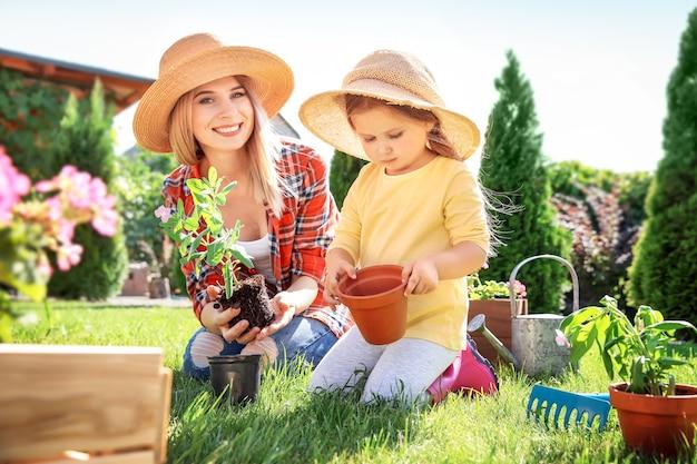 Menina bonitinha com a mãe cuidando das plantas no jardim em um dia ensolarado