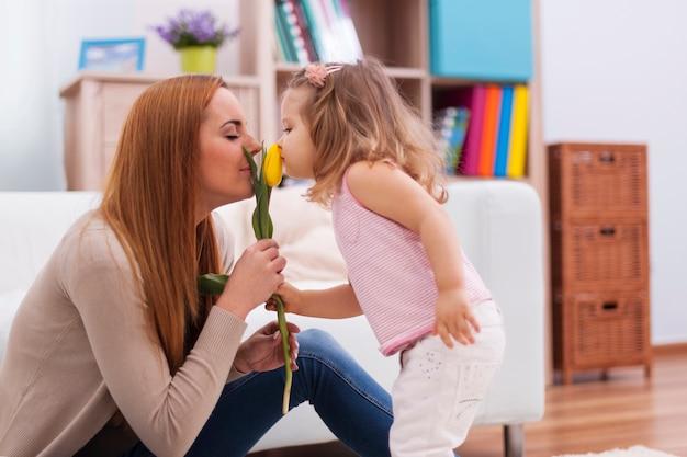 Menina bonitinha com a mãe sentindo o cheiro de tulipa fresca
