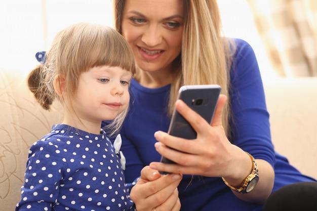 Menina bonitinha com a mãe sorridente usando smartphone