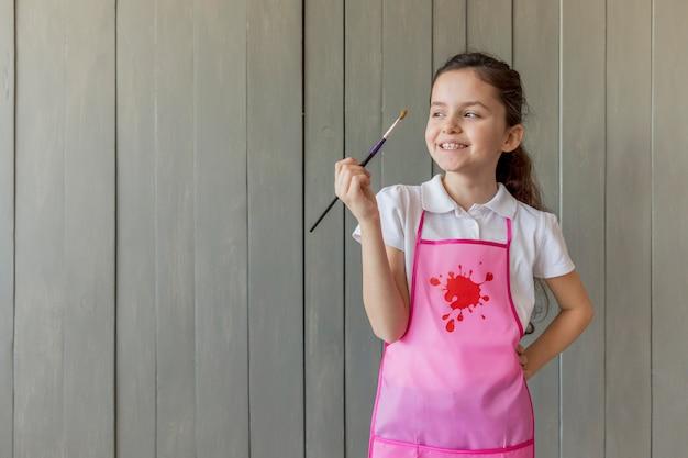Menina bonitinha com a mão na cintura, segurando o pincel em frente a parede de madeira cinza
