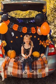 Menina bonitinha com abóboras comendo doces em baldes, sentada no porta-malas do carro