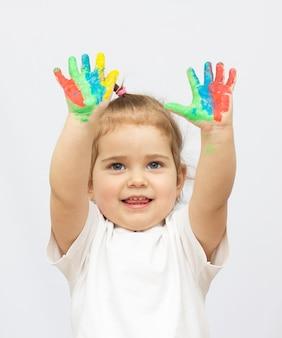Menina bonitinha com as mãos pintadas. isolado em um fundo branco.