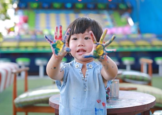 Menina bonitinha com as mãos pintadas