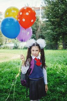 Menina bonitinha com balões coloridos perto da escola com uniforme escolar