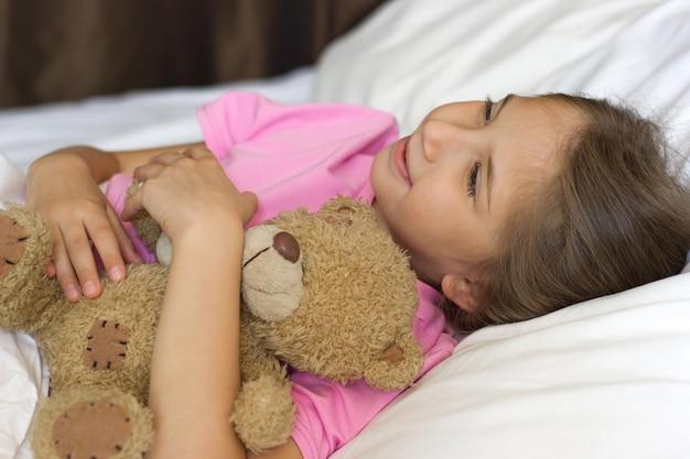 Menina bonitinha com cabelo loiro em uma camiseta rosa deitada na cama sorrindo, sonhando, abraçando um ursinho de pelúcia