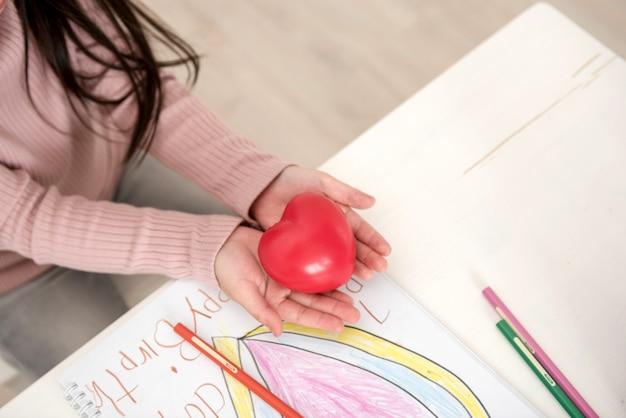 Menina bonitinha com cabelos compridos, brincando com um coração vermelho