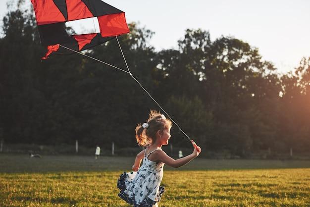 Menina bonitinha com cabelos longos, correndo com pipa no campo em dia de sol de verão