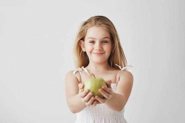 Menina bonitinha com cabelos longos loiros e olhos azuis em vestido branco sorrindo, segurando a maçã nas mãos e mostrando