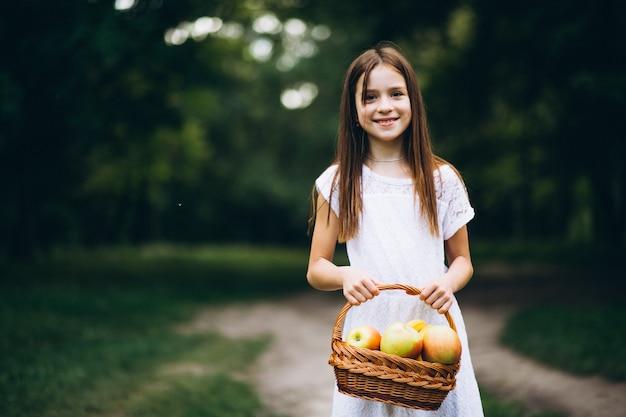 Menina bonitinha com cesta de frutas