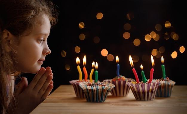 Menina bonitinha com chapéu de festa olhando as velas em bolos de aniversário.