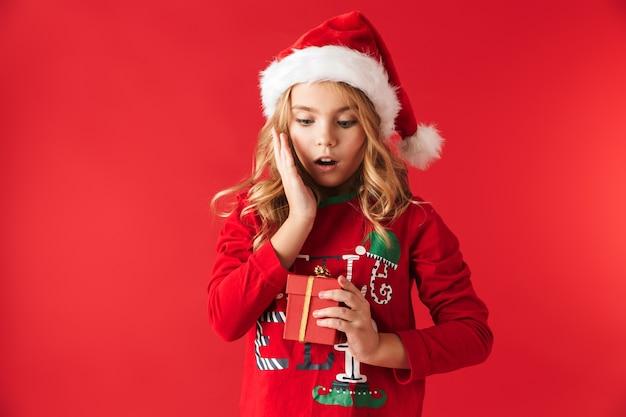 Menina bonitinha com chapéu de natal isolada, segurando uma caixa de presente