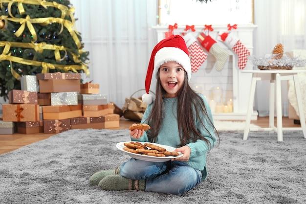 Menina bonitinha com chapéu de papai noel com prato de biscoitos deliciosos em casa