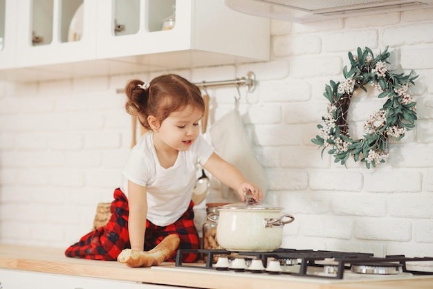 Menina bonitinha com chapéu de papai noel, preparando biscoitos na cozinha em casa. senta-se na mesa da cozinha e ajuda a mãe a preparar um jantar festivo de natal