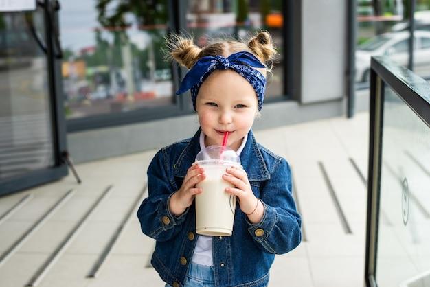 Menina bonitinha com coquetel de leite na rua