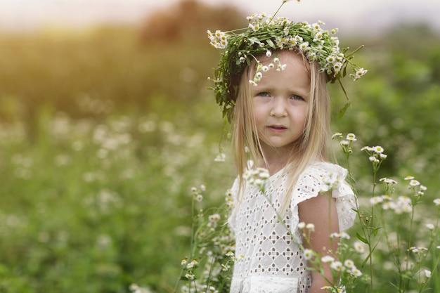 Menina bonitinha com coroa de flores no prado na fazenda.