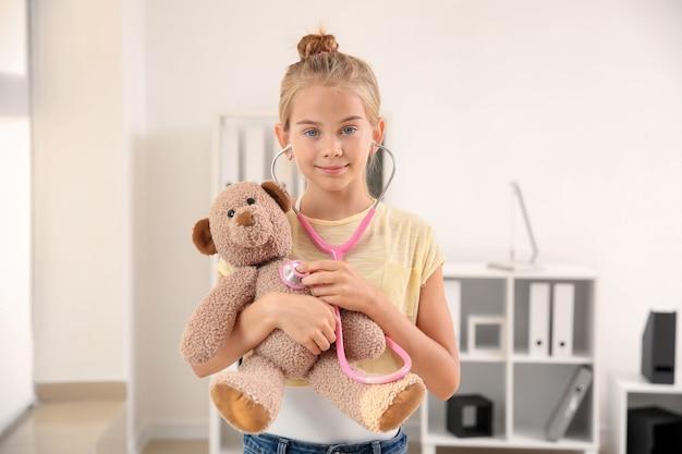Menina bonitinha com estetoscópio e ursinho de pelúcia em casa