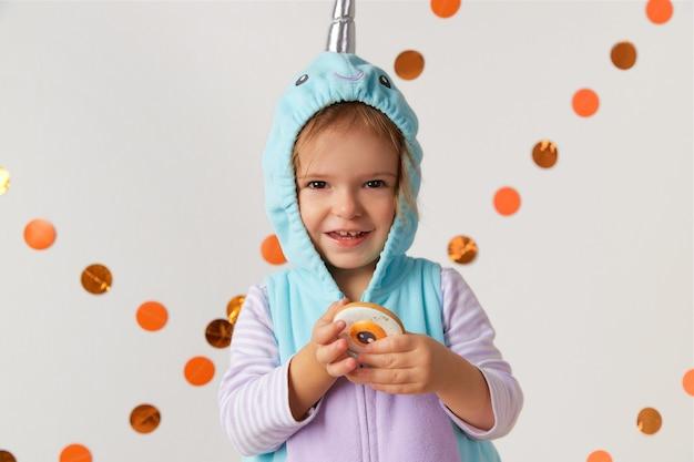 Menina bonitinha com fantasia de narval segurando biscoito em casa, festa de halloween