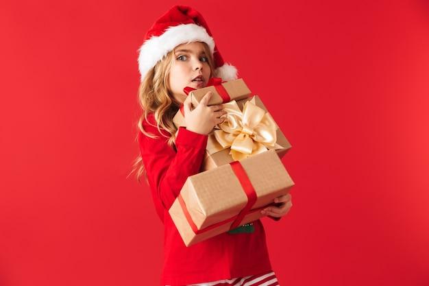 Menina bonitinha com fantasia de natal parada, isolada, segurando caixas de presente