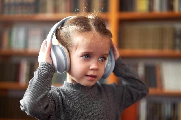 Menina bonitinha com fones de ouvido ouve música