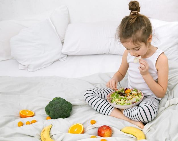 Menina bonitinha com frutas e legumes na luz.