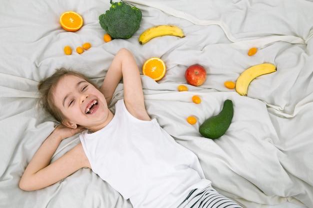 Menina bonitinha com frutas e legumes.