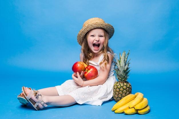 Menina bonitinha com frutas isoladas em uma parede azul