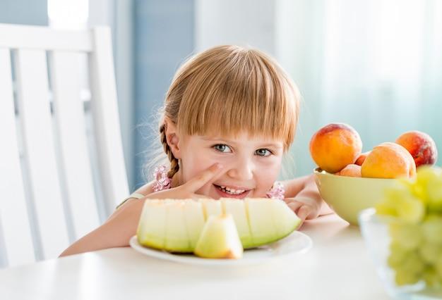 Menina bonitinha com frutas na mesa