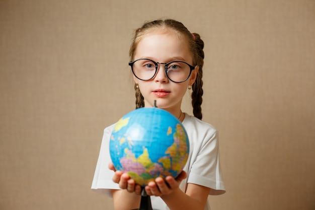 Menina bonitinha com globo. garota de criança com óculos em camiseta branca. conceito de educação escolar.