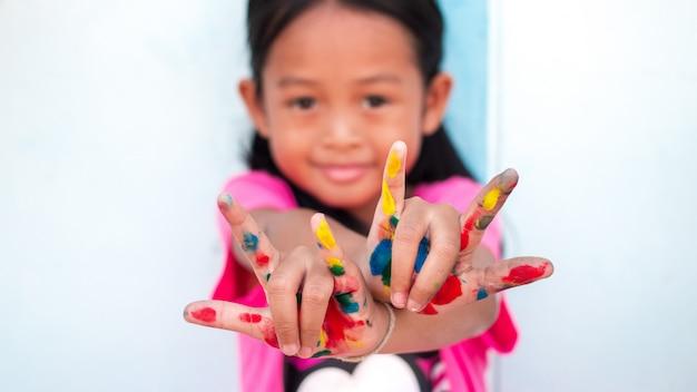 Menina bonitinha com mãos pintadas coloridas na parede