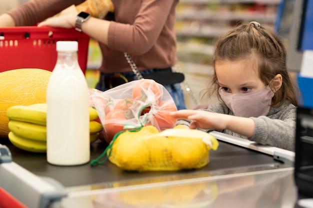 Menina bonitinha com máscara protetora olhando frutas e vegetais frescos no balcão enquanto estava na fila do supermercado com a mãe por perto