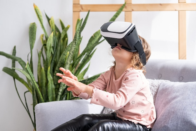 Menina bonitinha com óculos de realidade virtual em casa criança feliz usando fone de ouvido vr