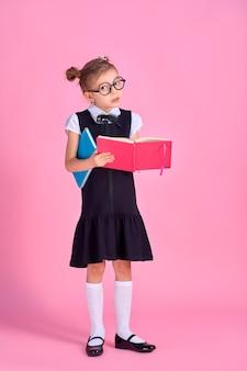 Menina bonitinha com óculos e livros sobre fundo rosa