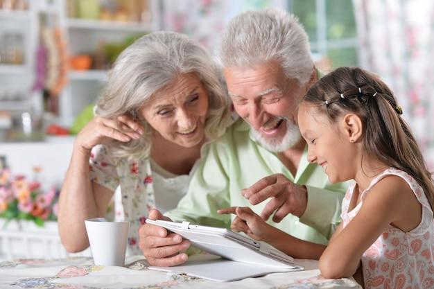Menina bonitinha com os avós usando um tablet moderno