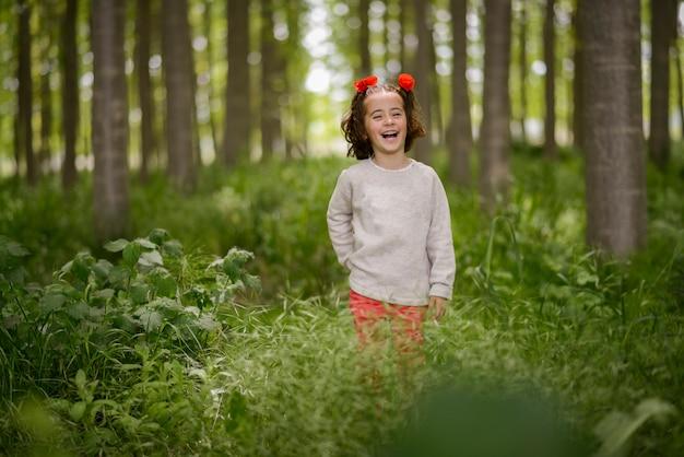 Menina bonitinha com quatro anos de idade se divertindo em uma floresta de choupos