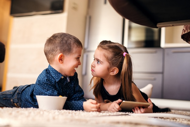 Menina bonitinha com rabos de cavalo olhando estranho para o irmão dela.