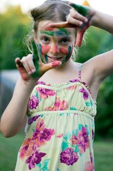 Menina bonitinha com rosto colorido e mãos fazendo um quadro de dedo