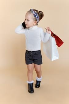 Menina bonitinha com roupa de outono segurando uma sacola de compras na mão