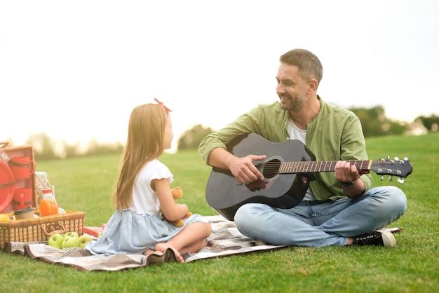 Menina bonitinha com roupas casuais, sentada em uma grama verde no parque e olhando para seu pai amoroso