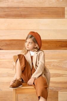 Menina bonitinha com roupas de outono sentada perto de uma parede de madeira