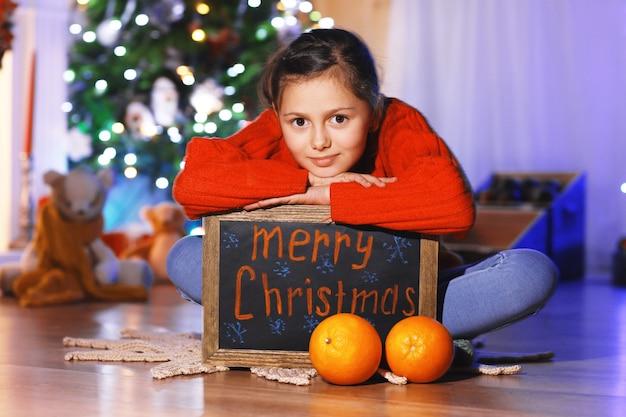 Menina bonitinha com saudação de feliz natal