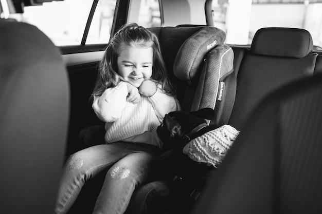 Menina bonitinha com seu animal de estimação sentado na parte de trás de um carro