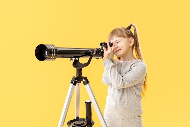 Menina bonitinha com telescópio na superfície colorida