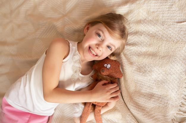 Menina bonitinha com um brinquedo macio no sofá