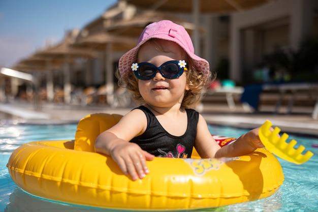 Menina bonitinha com um chapéu e óculos escuros brinca na piscina enquanto está sentado em um círculo de natação