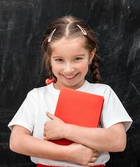 Menina bonitinha com um livro vermelho nas mãos na escola