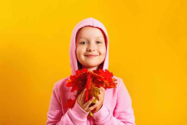 Menina bonitinha com uma braçada de folhas de maple outono