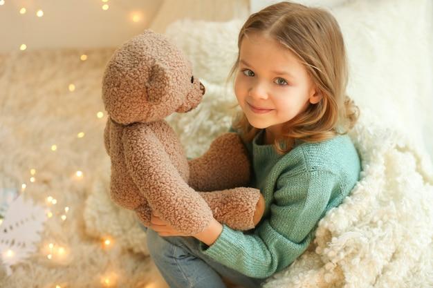 Menina bonitinha com ursinho de pelúcia em casa