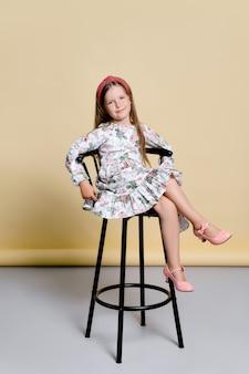 Menina bonitinha com vestido de verão e faixa de cabelo sentada em uma cadeira alta no estúdio sobre amarelo claro