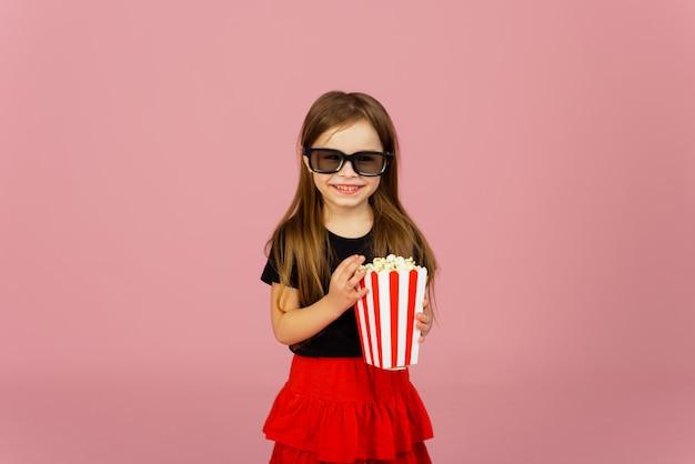 Menina bonitinha come pipoca de embalagens listradas e assiste a um filme com óculos 3d. conceito de publicidade de cinema, assistindo filme on-line