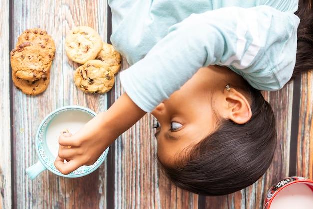 Menina bonitinha comendo biscoitos com leite